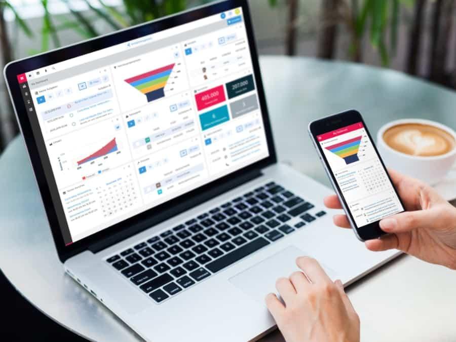 Detailaufnahme von Laptop und Mobiltelefon auf dem Display ist die CRM/xRM Software zu sehen