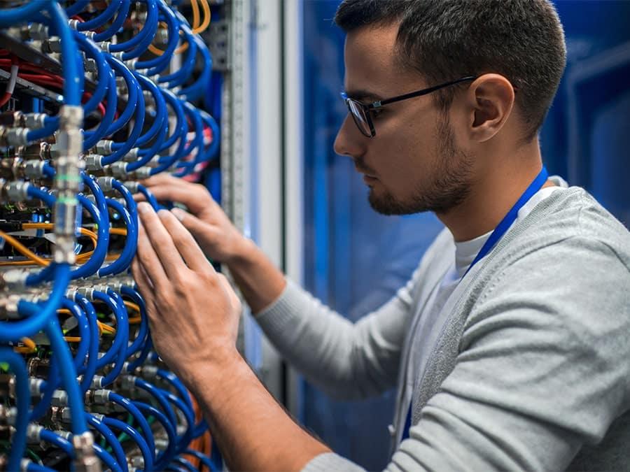 Junger IT Fachmann arbeitet an einem Server und prüft die Patchkabel