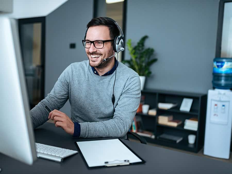 Mitarbeiter mit Headset im Bereich IT-Betreuung berät einen Kunden