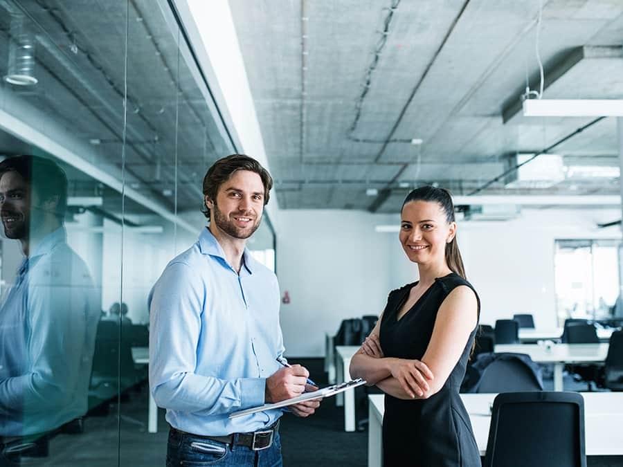 Zwei junge Mitarbeiter Mann und Frau stehen unterhalten sich im Großraumbüro