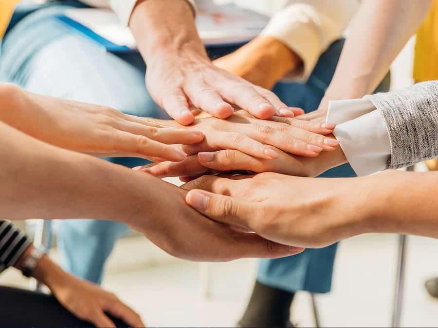 INES IT Team gibt sich die Hände - Zusammenhalt