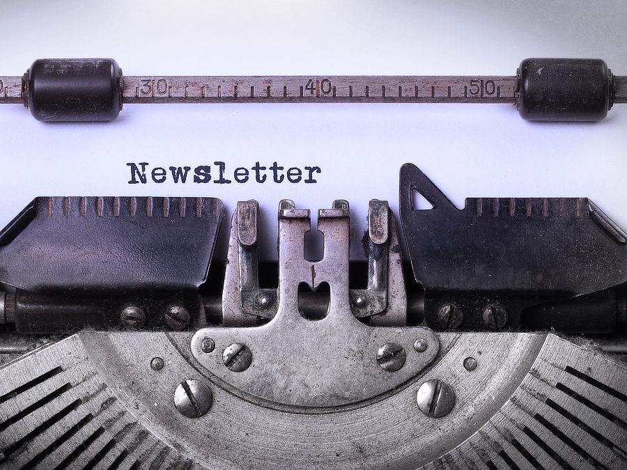 Grafik zeigt eine Detailaufnahme einer alten Schreibmaschine, auf dem Papier steht Newsletter geschrieben