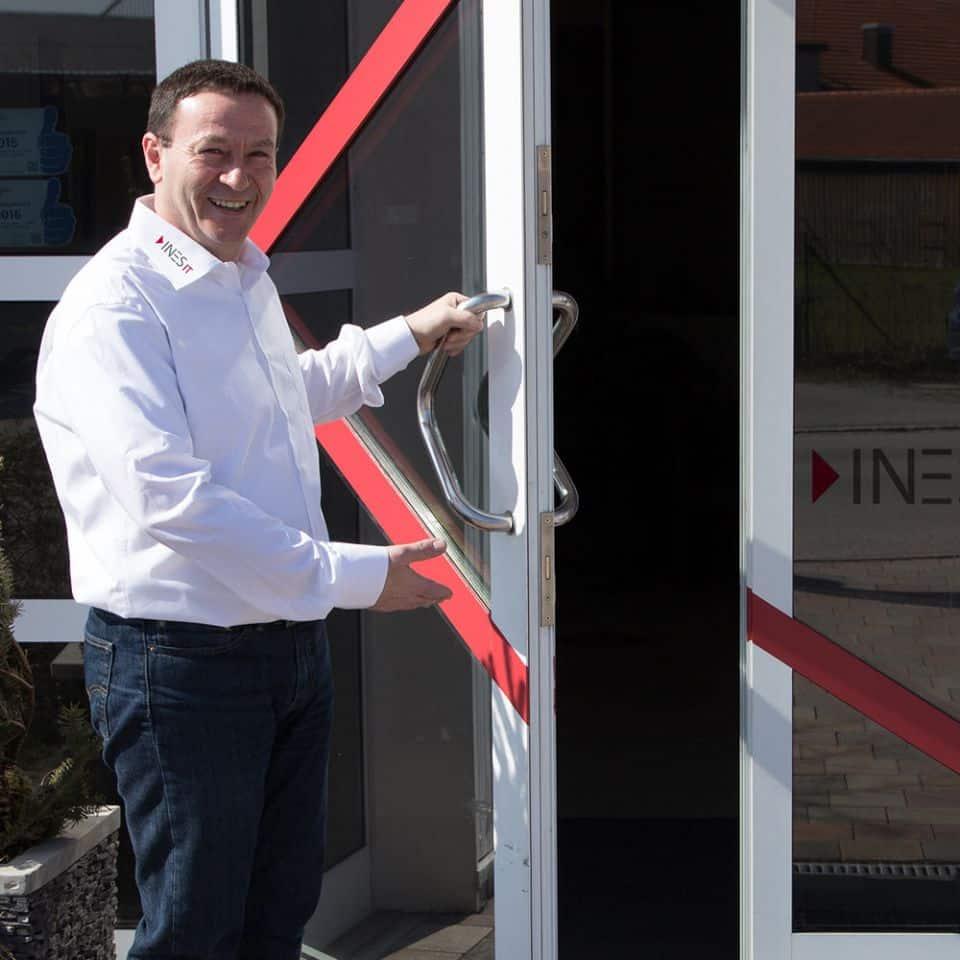 INES IT Mitarbeiter hält die Tür zum Firmengelände auf